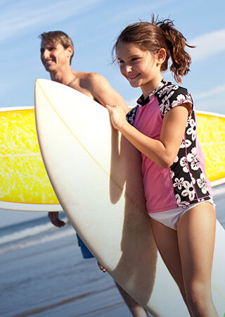 Young girl and Father walking with their surfboards.