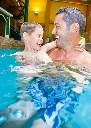 Father and Son swimming in pool.